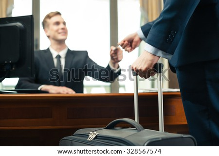 Blurred close up photo of receptionist and client in expensive hotel. Customer with suitcase giving his credit card to receptionist