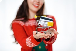 Blurred close up portrait of smiling woman in a new year's sweater, holding a mini-cart with a bank card. White background. The concept of the Christmas sales