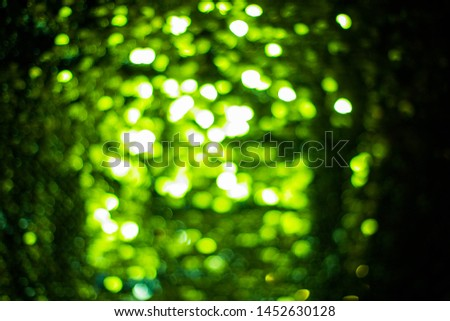 Blurred colored bokeh on black background. Glowing bokeh lights in the dark, reflections and highlights of different colors. Garland glows at night #1452630128