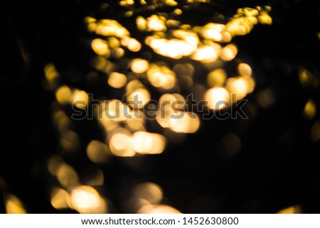 Blurred colored bokeh on black background. Glowing bokeh lights in the dark, reflections and highlights of different colors. Garland glows at night #1452630800
