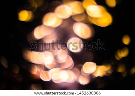 Blurred colored bokeh on black background. Glowing bokeh lights in the dark, reflections and highlights of different colors. Garland glows at night #1452630806