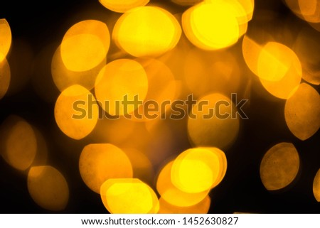 Blurred colored bokeh on black background. Glowing bokeh lights in the dark, reflections and highlights of different colors. Garland glows at night #1452630827