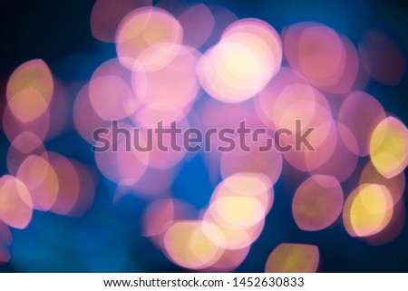 Blurred colored bokeh on black background. Glowing bokeh lights in the dark, reflections and highlights of different colors. Garland glows at night #1452630833