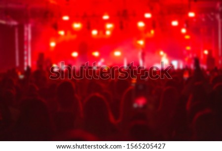 Photo of Blurred concert background with group of music fans partying in bright red stage lights.Out of focus backdrop for musical festival poster.Place text on blurry image
