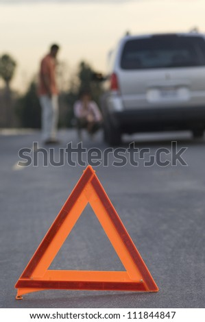 Blurred couple in discussion with warning triangle in foreground