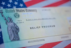 Blurred COVID-19 economic Stimulus American rescue program check on blurred USA flag and sun light background. Relief program concept.