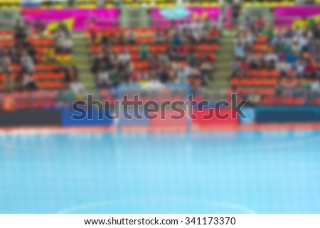 Blurred crowd of spectators in the indoor stadium with futsal match.