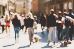 Blurred crowd of walking people in the city with buildings in the background