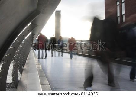 blurred crowd on millennium bridge with tate modern in background