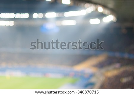 Blurred crowded football stadium with field, stands and spectators. 2016 sport background.