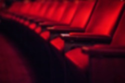 Blurred dark background: row of empty red theater chairs