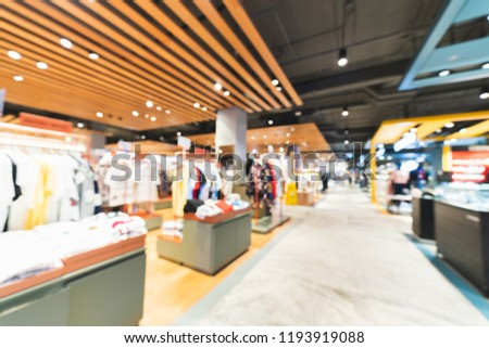 Blurred, defocused background of clothing shops in modern shopping mall or department store. Shopaholic lifestyle, or fashion dress outlet business concept #1193919088