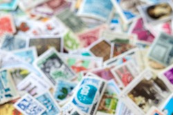 Blurred defocused background texture from old multicolored postage stamps collection from different countries