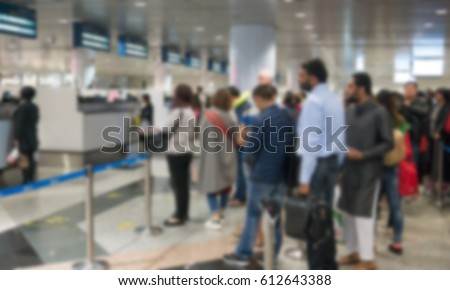 Blurred defocused image of group travellers queue at immigration control at airport for background.