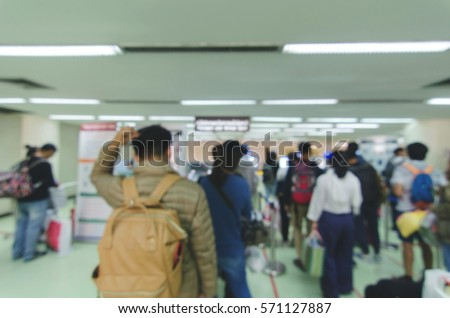 Blurred defocused image of travellers queue at immigration control at airport, for background, color tone effect.