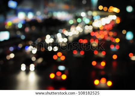 Blurred Defocused Lights of Heavy Traffic on a Wet Rainy City Road at Night - Commuting at Rush Hour Concept