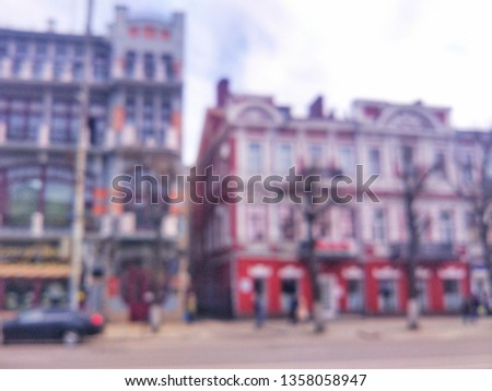 Blurred defocused photograph of the road, houses and cars on Revolution Avenue - the main street of the city of Voronezh, Russia. #1358058947