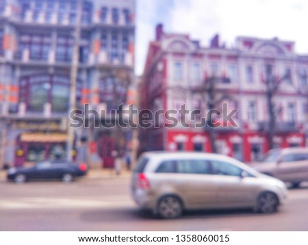 Blurred defocused photograph of the road, houses and cars on Revolution Avenue - the main street of the city of Voronezh, Russia. #1358060015