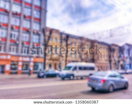 Blurred defocused photograph of the road, houses and cars on Revolution Avenue - the main street of the city of Voronezh, Russia. #1358060387