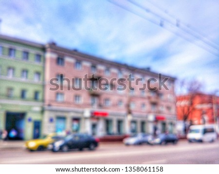 Blurred defocused photograph of the road, houses and cars on Revolution Avenue - the main street of the city of Voronezh, Russia. #1358061158