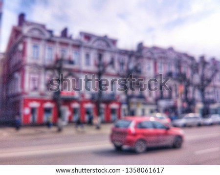 Blurred defocused photograph of the road, houses and cars on Revolution Avenue - the main street of the city of Voronezh, Russia. #1358061617