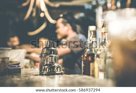 Blurred defocused side view of barman and guests drinking and having fun at cocktail bar - Social gathering concept with people enjoying time together - Warm retro contrast filter with focus on shaker