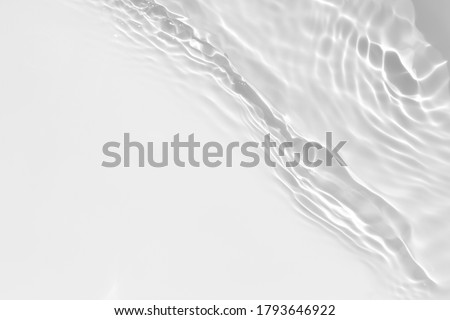 Blurred desaturated transparent clear calm water surface texture with splashes and bubbles. Trendy abstract nature background. White-grey water waves in sunlight.