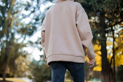 blurred details of oversized hoodie  at model in lights. Back view at a man  in oversize hoodie.fashion and wear concept.warm oversized wear at girl.space for text and logo.back view of beige hoodie.