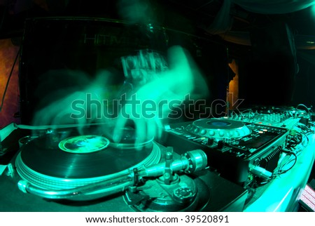 blurred dj at spin table in night club