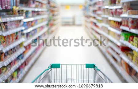 Blurred effect in the Supermarket aisle with empty silver and green shopping trolley,  Shopper choosing the food in supermarket Panic buyer for hoarding food, Coronavirus Covid-19 concept.