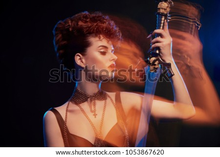 Blurred effect of sexy warrior woman keeping steel sword with black skulls. Girl wearing thin chain on neck. Model wears bright make up with red lipstick and original hairdress with little curles. #1053867620