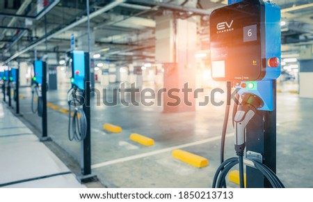 Blurred electric car charging station for charge EV battery. Plug for vehicle with electric engine. EV charger. Clean energy. Charging point at car parking lot. Future transport technology. Stockfoto ©