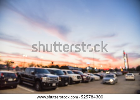 Blurred exterior view of modern shopping center in Humble, Texas, US at sunset. Mall complex with row of cars in outdoor uncovered parking lots, bokeh of retail store and light poles in background. #525784300
