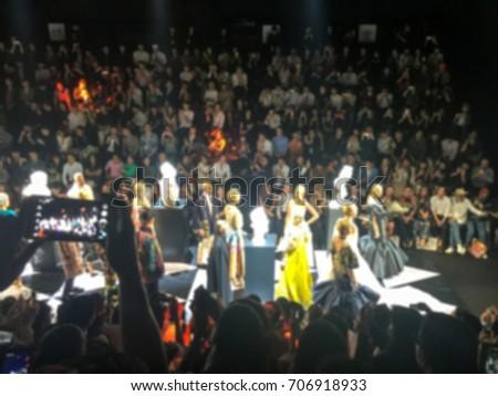 Blurred Fashion show runway , catwalk event , Spectators enjoy watching and taking photo models walk #706918933