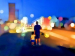 Blurred father and son holding hands on the side of the road at night with abstract bokeh lights.Protect and be careful for the safety.happy father's day concept