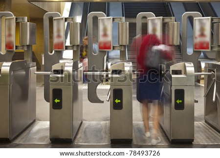 Blurred figure of person passing through subway turnstiles