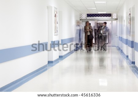 blurred figures of doctor and patients walking in a hospital corridor