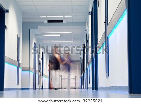 blurred figures of nurses walking down a hospital corridor