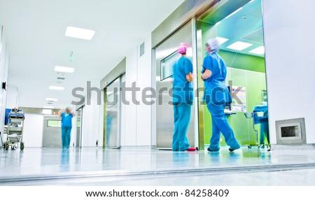 blurred figures wearing medical uniforms in hospital surgery corridor