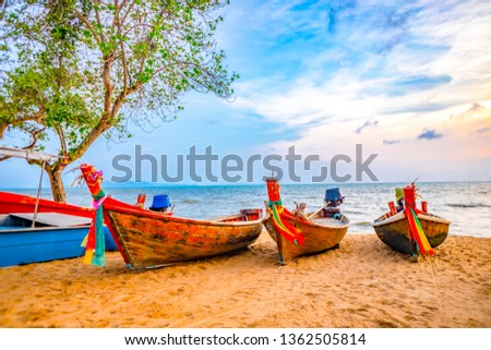 Blurred fisherman boats on sand beach of sea on blue sea and blue sky background on sunset #1362505814