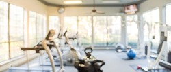 Blurred fitness center with cardio machines and weight, strength training equipment. Empty gym facility service room in apartment building complex at Houston, Texas, US. Panorama banner presentation.