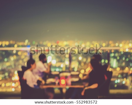 Blurred focus of rooftop restaurant with people dinning at night, vintage filtered #552983572