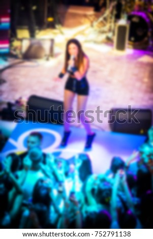 Blurred for background. Ibiza club. Artist performs songs and dance show from stage during concert at nightclub. Artist on club stage during night party.