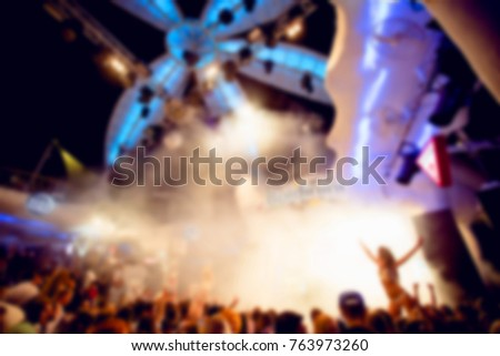Blurred for background. Ibiza Night club dj party people enjoy of music dancing sound with colorful light, Smoke Machine, lights show and go go dancer. Night party in night club. #763973260