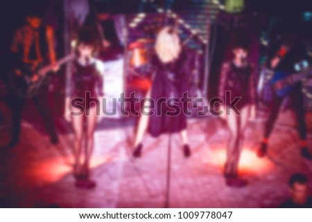 Blurred for background night club. Artist performs songs and club show from stage during concert at nightclub. Artist on club stage during night party. #1009778047