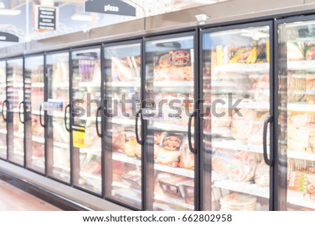 Blurred frozen food section at retail store in America. Huge glass door aisle with variety pack of processed pizza. Freezer full assortment of frozen pizza in local supermarket, defocused background.