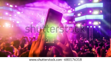 Blurred girl hands making video of summer festival concert with mobile phone - Crowd celebrating party event - Defocused image - Concept of fun, music and entertainment - Original color lights