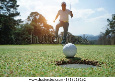 Blurred Golfer putting ball on the green golf, lens flare on sun set evening time. Golfer action to win after long putting golf ball in to the hole.                                Stockfoto ©