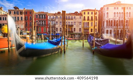Blurred gondolas in Venice, typical ancient palaces in background in sunset. #409564198