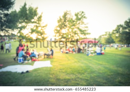 Blurred group of African American friend, family members enjoy free outdoor music festival, open-air concert held in public park at Houston. Audience sits on the chairs, grass, open tent. Vintage tone #655485223